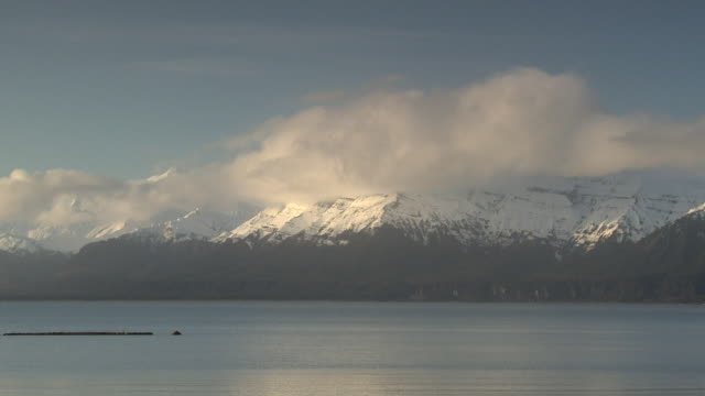 Low clouds churn over snowy mountains and a bay in Alaska.