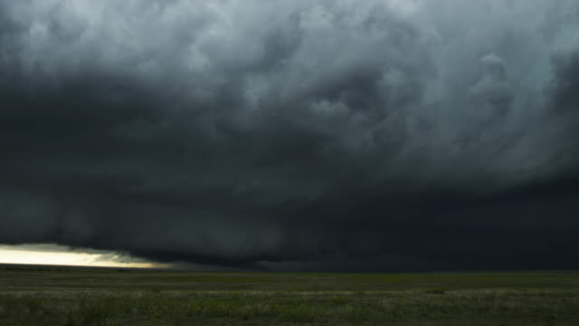 Low fast-moving shelf cloud almost touches windy prairie, time lapse