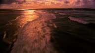 AERIAL low over beach + water at sunset / Ireland