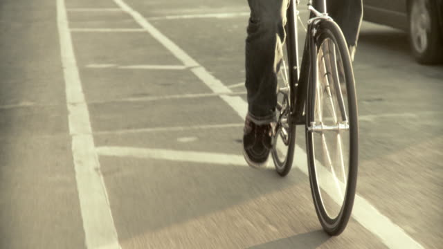 CU POV Low section of man riding bicycle on street, Brooklyn, New York City, New York State, USA