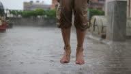 Frau Beine springen im Regen