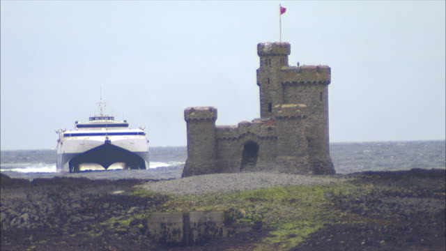 WS Castle on exposed reef St Mary's Isle seabirds flying FG commercial passenger catamaran SeaCat ferry boat approaching BG
