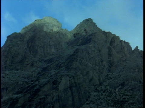 Low WA view of craggy mountain top set against blue sky, Uganda, Africa