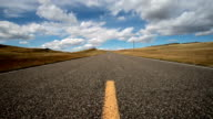 Low wide angle view of empty paved road with puffy clouds and blue sky with shadows rolling across landscape.