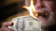 Low-angle close-up of man with grey beard lighting cigar with US$100 bill