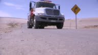 Low-angle sequence showing a modern heavy-goods vehicle travelling on roads in the Atacama Desert, Chile.
