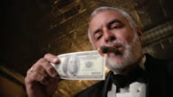 Low-angle shot of man in tuxedo lighting cigar with US$100 bill