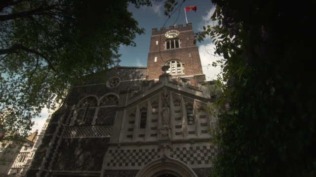 Low-angle track and dolly shot approaching the facade of St Bartholomew the Great Church in the City of London, UK.