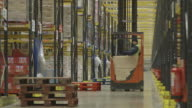 Low-level, angled wide shot of a long central corridor in a food distribution warehouse taken with a telephoto lens, UK.