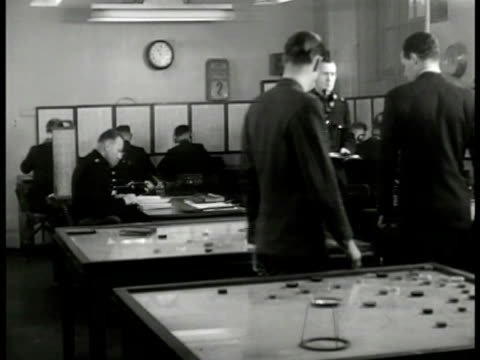 WS 'Lt Roberts' and 'Inspector Finch' looking at table map English policemen radiomen MS Policeman looking at map through table magnifying glass CU...