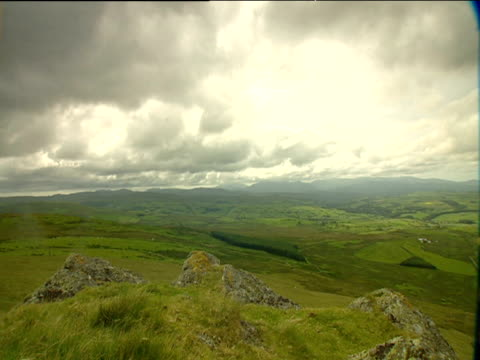 Lush green valleys with mountains in background and heavy grey clouds above zoom in to mountains