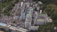 Lush vegetation surrounds the sprawling campus of the National Cerebral and Cardiovascular Center in Osaka, Japan.