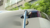 CLOSE UP: Luxury electric car has charging cable plugged in, filling battery at home