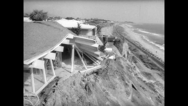 Luxury homes crumbling along Pacific Coast in San Clemente due to landslide damage / houses on edge of steep mud bank close to ocean / CU broken...