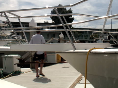 Luxury Lifestyle: Man on Dock - Passes Boat Bow