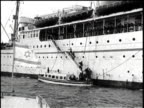 A luxury liner on the ocean shot from the bow / people line the rails looking out / women with children and men sit together in their coats / a...