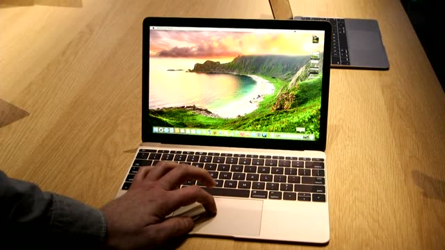 A MacBook laptop on a table in New York City on March 9th 2015 No Sound Shots Interior close shot of a mans hand opening a macbook Wide shot of the...