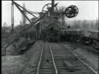 Machine and workers help dredge harbor near railroad tracks / France