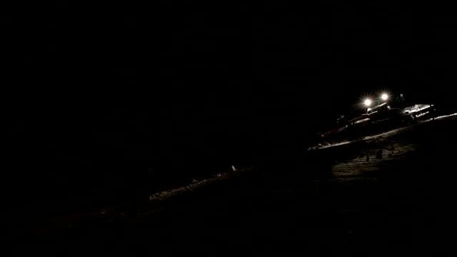 Machine voor de herverdeling van de ski pistes werken 's nachts.