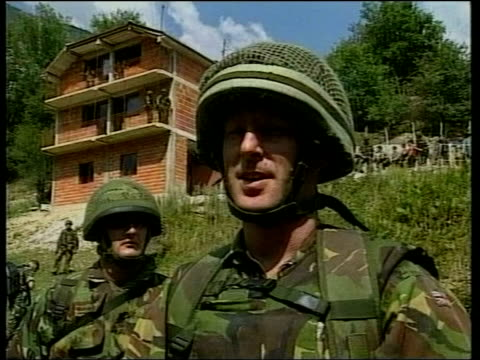 Machine gun pointing out of door of helicopter as flying over countryside AIR VIEW Albanian Liberation Army members queuing to hand in weapons MS...