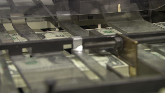 A machine processes newly printed US dollar bills.