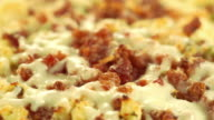 ECU macro shot of cheese and bacon bits on pizza bubbling from extreme heat