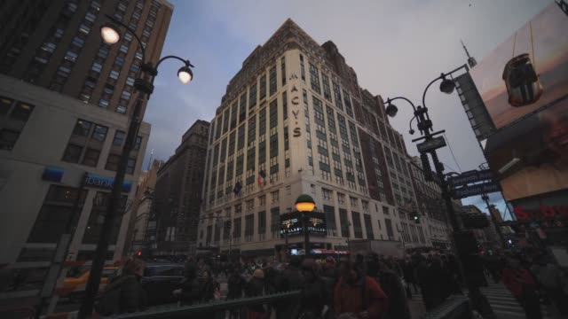 Macy's flagship store in New York NY US on February 24 Wide shot pans of Macy's in Herald Square as pedestrians pass by with cloud movement in the...