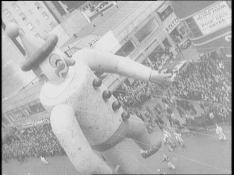Macy's Thanksgiving parade heralds Christmas season / large float of comic book hero is pulled down the street during Macy's parade / kids look up at...