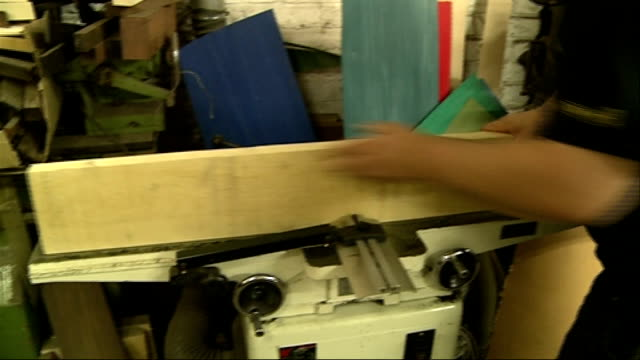 'Made in London' series Snooker cue maker Finished snooker cues propped up worker making cue worker operating machinery finished cues propped up wood...