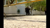 EXT Portuguese police officers searching local area Hotel complex with police cordon in foreground where McCann family were staying Police officers...