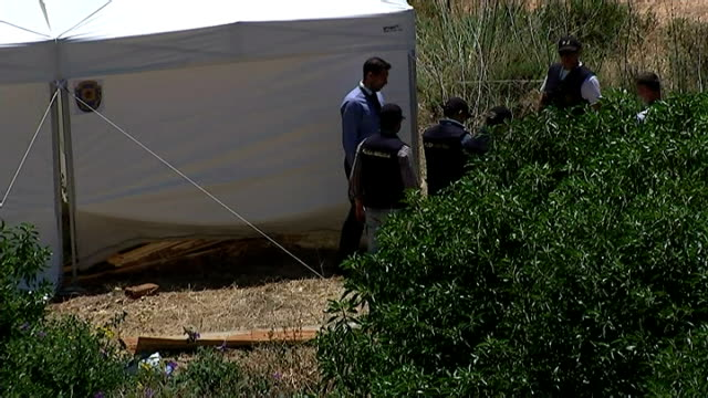 British police at search site Forensic and police officers along next to tent / View over apartments to coast and forensic tent towards blue sea