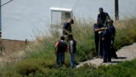 British police at search site Various of police officers cutting down greenery at site and searching undergrowth / police officers chatting at search...