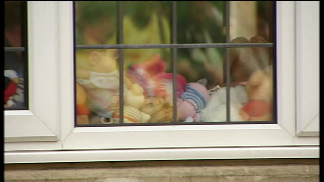 Family arrival at home village of Rothley Pile of children's toys seen through house window