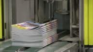 CU Magazines passing on conveyor belt in gravure printing office / Itzehoe, Schleswig-Holstein, Germany