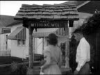 WS 'Magic Wishing Well' sign outside small chapel newly married couple 'Dottie amp Gordon Wilson' kissing in front of well walking to convertible car...