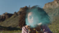 SLO MO. Magical young woman blows blue sand at camera and laughs in beautiful desert.