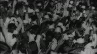 Mahatma Gandhi walking through crowd of people / India