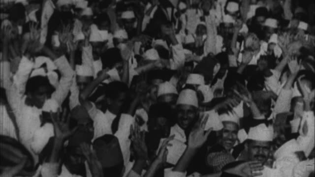 Mahatma Gandhi walking through crowd of people / India