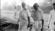Mahatma Gandhi walks with his wife Kasturba Gandhi and others
