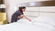 Zimmermädchen arbeiten in einem Hotel, das Bett machen