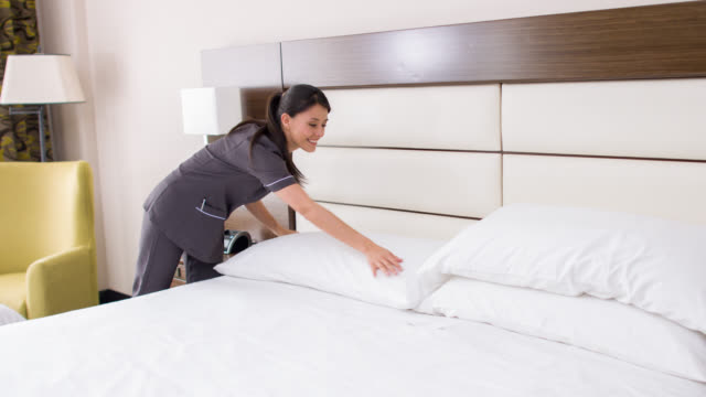 Maid working at a hotel making the bed