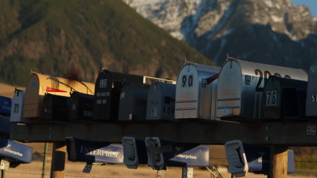 Mail boxes in front of mountain as night falls.