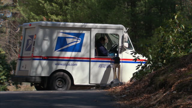 LA US Mail truck driving up to mailbox, delivering mail, and driving off / Marshfield, Massachusetts, United States
