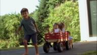 MS, USA, Maine, Yarmouth, Boy (6-7) pulling wagon with three children (2-3, 4-5) on driveway
