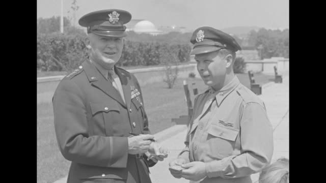 CU Maj Richard Bong World War II ace combat pilot stands on airstrip in Washington DC / 2shot Bong with Gen Henry 'Hap' Arnold who signs a dollar...