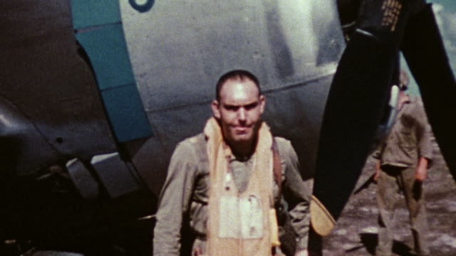 Major HE McAfee standing beside P47 Thunderbolt 'Jeanie' during WWII pilot in fighter and taxiing across airfield