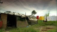 Makeshift shanty house in grassy rural area clothes line extending from house colorful clothing on line moving in wind dark clouds BG Laundry poverty