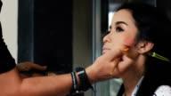 Make up und Pinsel Bewegung der jungen Asiatin