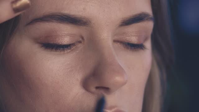 Makeup artist applying cosmetics on eyelash