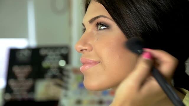 Make-up Künstler Anwendung Gesichtspuder auf wunderschöne junge model